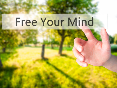 position d amour: Free Your Mind - Hand pressing a button on blurred background concept . Business, technology, internet concept. Stock Photo