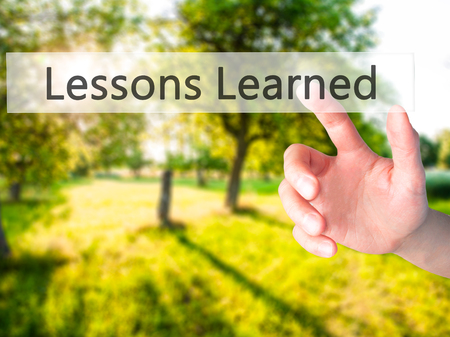 recap: Lessons Learned - Hand pressing a button on blurred background concept . Business, technology, internet concept. Stock Photo