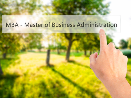 MBA - Master of Business Administration - Hand pressing a button on blurred background concept . Business, technology, internet concept. Stock Photo