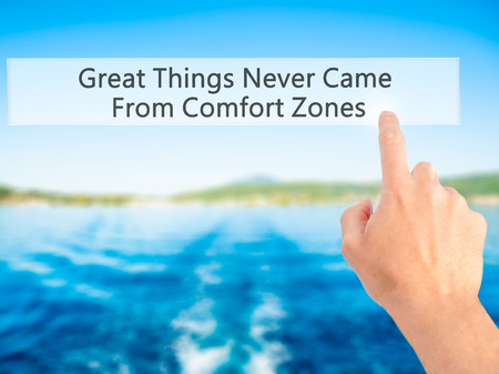 Great Things Never Came From Comfort Zones - Hand pressing a button on blurred background concept . Business, technology, internet concept. Stock Photo