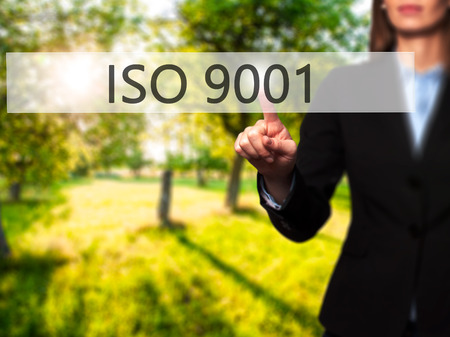 ISO 9001 - Businesswoman hand pressing button on touch screen interface. Business, technology, internet concept. Stock Photo