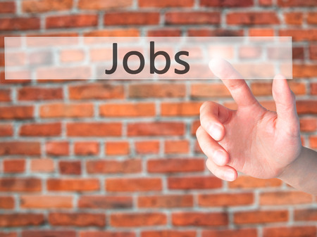 joblessness: Jobs - Hand pressing a button on blurred background concept . Business, technology, internet concept. Stock Photo