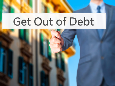 bank records: Get Out of Debt - Business man showing sign. Business, technology, internet concept. Stock Photo