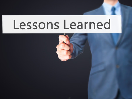 recap: Lessons Learned - Business man showing sign. Business, technology, internet concept. Stock Photo