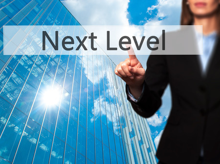 Next Level - Businesswoman pressing modern  buttons on a virtual screen. Concept of technology and  internet. Stock Photo