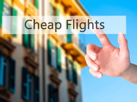 low price: Cheap Flights - Hand pressing a button on blurred background concept . Business, technology, internet concept. Stock Photo