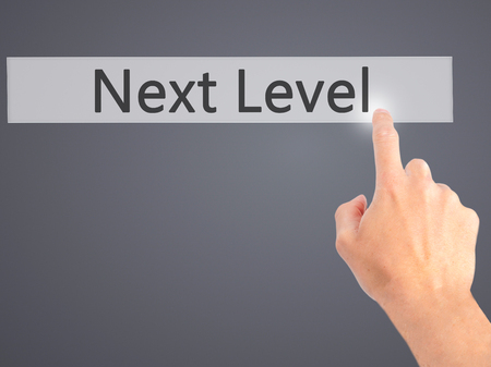 aim: Next Level - Hand pressing a button on blurred background concept . Business, technology, internet concept. Stock Photo