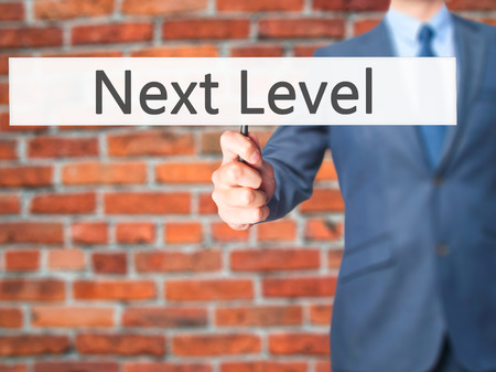 higher intelligence: Next Level - Business man showing sign. Business, technology, internet concept. Stock Photo Stock Photo