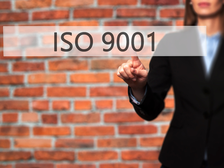 certify: ISO 9001 - Businesswoman hand pressing button on touch screen interface. Business, technology, internet concept. Stock Photo