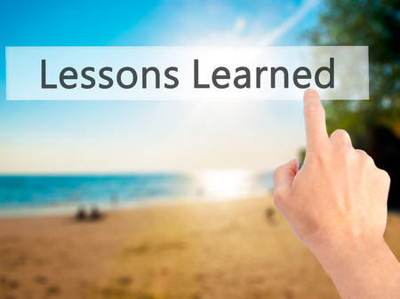 summarize: Lessons Learned - Hand pressing a button on blurred background concept . Business, technology, internet concept. Stock Photo