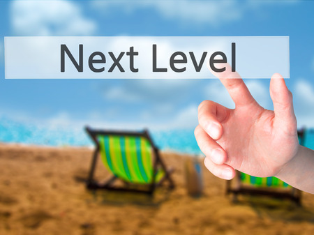 Next Level - Hand pressing a button on blurred background concept . Business, technology, internet concept. Stock Photo