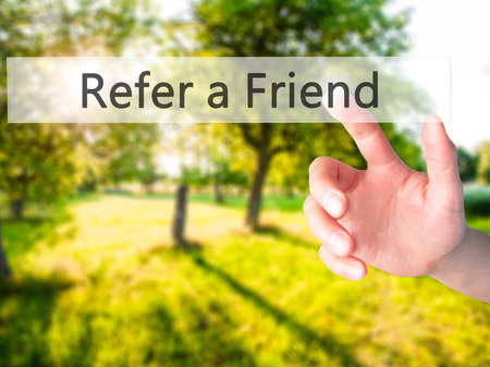 Refer a Friend - Hand pressing a button on blurred background concept . Business, technology, internet concept. Stock Photo