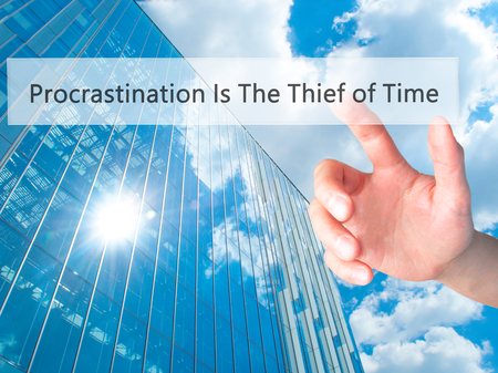 procrastination: Procrastination Is The Thief of Time - Hand pressing a button on blurred background concept . Business, technology, internet concept. Stock Photo Stock Photo