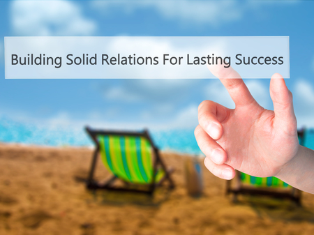 Building Solid Relations For Lasting Success - Hand pressing a button on blurred background concept . Business, technology, internet concept. Stock Photo