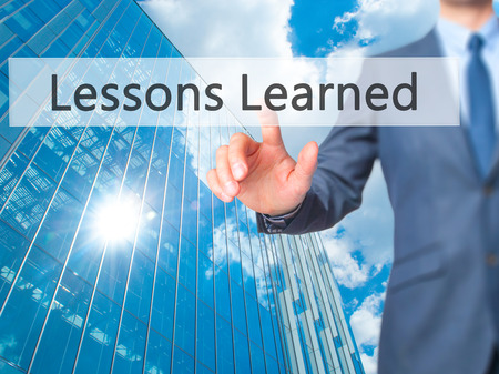summarize: Lessons Learned - Businessman press on digital screen. Business,  internet concept. Stock Photo