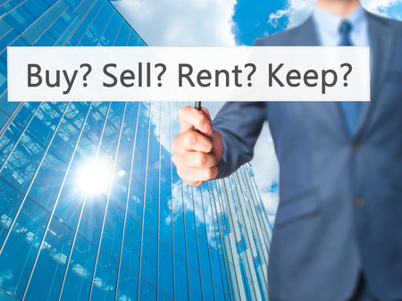 news values: Buy? Sell? Rent? Keep? - Business man showing sign. Business, technology, internet concept. Stock Photo