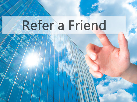 refer: Refer a Friend - Hand pressing a button on blurred background concept . Business, technology, internet concept. Stock Photo