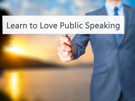 extrovert: Learn to Love Public Speaking - Businessman hand holding sign. Business, technology, internet concept. Stock Photo