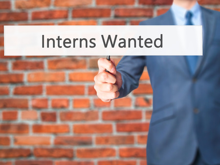apprenticeship employee: Interns Wanted - Businessman hand holding sign. Business, technology, internet concept. Stock Photo