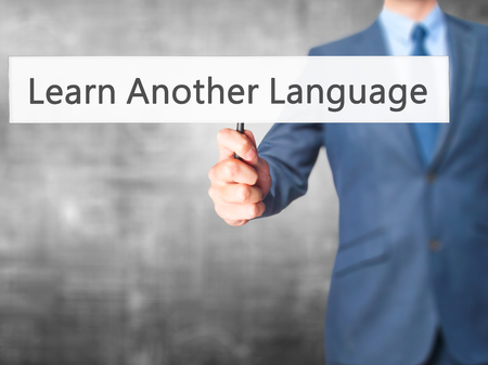 another: Learn Another Language - Businessman hand holding sign. Business, technology, internet concept. Stock Photo Stock Photo