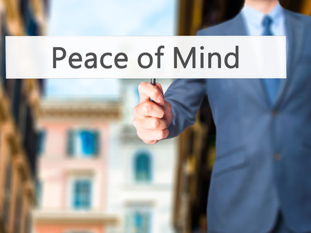 sense of security: Peace of Mind - Businessman hand holding sign. Business, technology, internet concept. Stock Photo