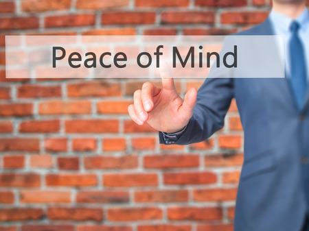 sense of security: Peace of Mind - Businessman hand pressing button on touch screen interface. Business, technology, internet concept. Stock Photo