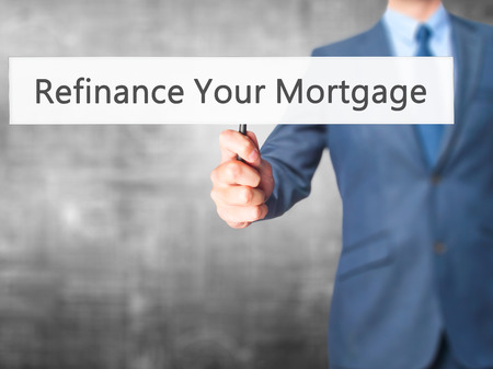 refinancing interest rates: Refinance Your Mortgage - Businessman hand holding sign. Business, technology, internet concept. Stock Photo