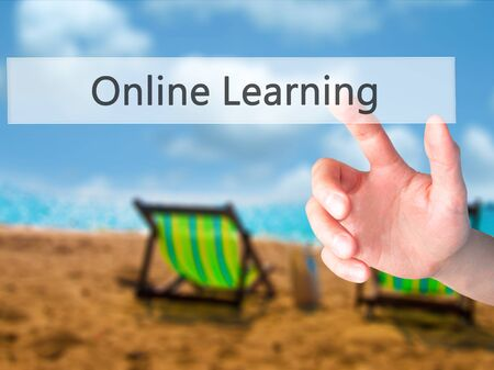 Online Learning - Hand pressing a button on blurred background concept . Business, technology, internet concept. Stock Photo Stock Photo