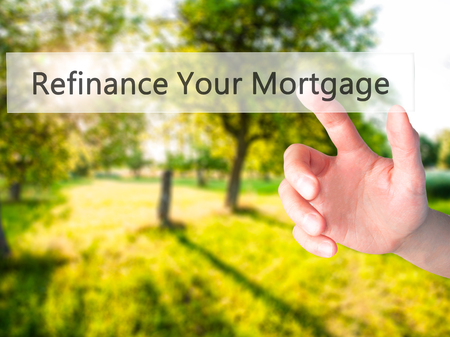Refinance Your Mortgage - Hand pressing a button on blurred background concept . Business, technology, internet concept. Stock Photo