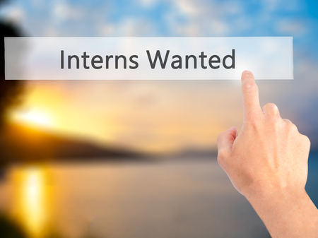 apprenticeship employee: Interns Wanted - Hand pressing a button on blurred background concept . Business, technology, internet concept. Stock Photo Stock Photo