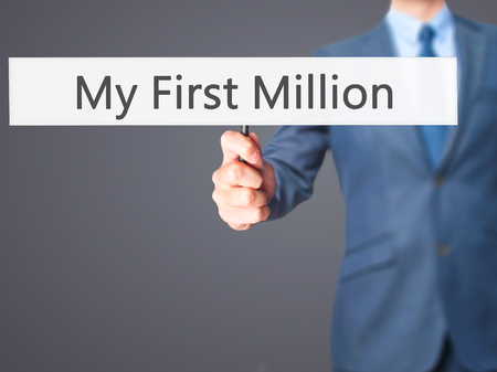 MILLION: My First Million - Businessman hand holding sign. Business, technology, internet concept. Stock Photo
