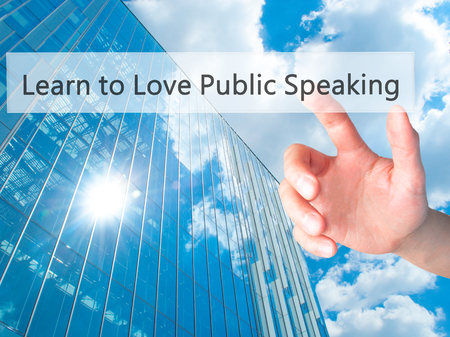 extrovert: Learn to Love Public Speaking - Hand pressing a button on blurred background concept . Business, technology, internet concept. Stock Photo