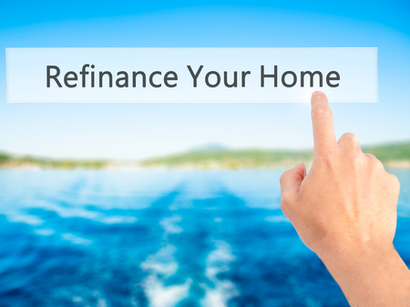 loaning: Refinance Your Home - Hand pressing a button on blurred background concept . Business, technology, internet concept. Stock Photo