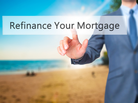 lender: Refinance Your Mortgage - Businessman hand pressing button on touch screen interface. Business, technology, internet concept. Stock Photo