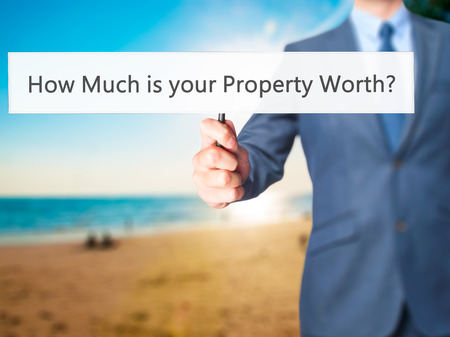cost estimate: How Much is your Property Worth? - Businessman hand holding sign. Business, technology, internet concept. Stock Photo
