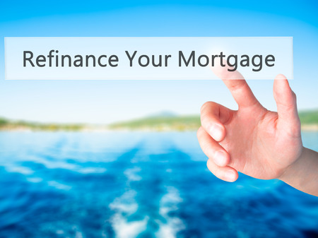 refinancing interest rates: Refinance Your Mortgage - Hand pressing a button on blurred background concept . Business, technology, internet concept. Stock Photo