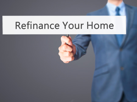loaning: Refinance Your Home - Businessman hand holding sign. Business, technology, internet concept. Stock Photo Stock Photo