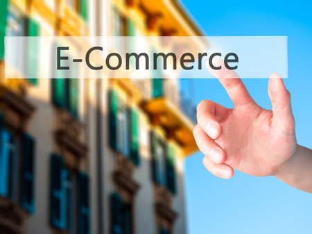 E-Commerce - Hand pressing a button on blurred background concept . Business, technology, internet concept. Stock Photo