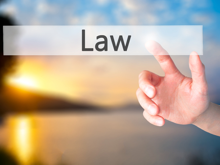 lawful: Law - Hand pressing a button on blurred background concept . Business, technology, internet concept. Stock Photo