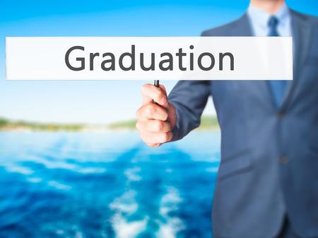 university admission: Graduation - Business man showing sign. Business, technology, internet concept. Stock Photo Stock Photo