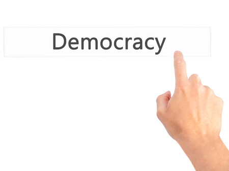 nomination: Democracy - Hand pressing a button on blurred background concept . Business, technology, internet concept. Stock Photo