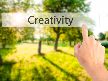 Creativity - Hand pressing a button on blurred background concept . Business, technology, internet concept. Stock Photo Stock Photo