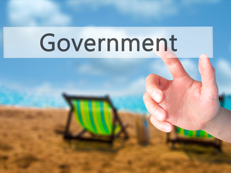 Government - Hand pressing a button on blurred background concept . Business, technology, internet concept. Stock Photo