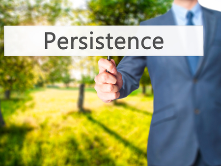 persistence: Persistence - Businessman hand holding sign. Business, technology, internet concept. Stock Photo Stock Photo