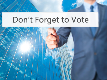 govern: Dont Forget to Vote - Businessman hand holding sign. Business, technology, internet concept. Stock Photo