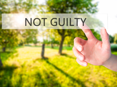NOT GUILTY - Hand pressing a button on blurred background concept . Business, technology, internet concept. Stock Photo