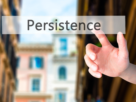 persist: Persistence - Hand pressing a button on blurred background concept . Business, technology, internet concept. Stock Photo Stock Photo