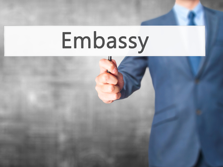 diplomat: Embassy - Businessman hand holding sign. Business, technology, internet concept. Stock Photo