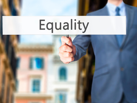 impartial: Equality - Businessman hand holding sign. Business, technology, internet concept. Stock Photo Stock Photo