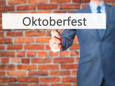 bier festival: Oktoberfest - Businessman hand holding sign. Business, technology, internet concept. Stock Photo